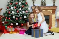 Gemelos de las muchachas con el árbol de navidad de los regalos e Imagen de archivo