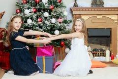 Gemelos de las muchachas con el árbol de navidad de los regalos e Foto de archivo