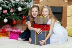 Gemelos de las muchachas con el árbol de navidad de los regalos e Fotografía de archivo libre de regalías