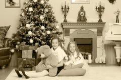 Gemelos de las muchachas con el árbol de navidad de los regalos e Foto de archivo libre de regalías