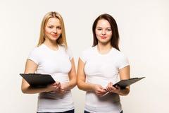 Gemelos de las muchachas con plagshety en manos Foto de archivo