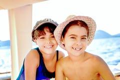 gemelos de las niñas con los sombreros del verano en una mirada descolorada Foto de archivo