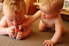 Gemelos del bebé que juegan con el juguete Fotos de archivo libres de regalías