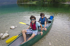 Gemelos felices alistan para canoe en el lago Bohinj, Eslovenia Fotografía de archivo libre de regalías