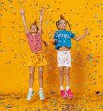 Gemelos felices de las muchachas de los niños el los días de fiesta que saltan en confeti multicolor en amarillo foto de archivo
