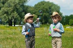 Gemelos idénticos con las burbujas de jabón Imagen de archivo libre de regalías