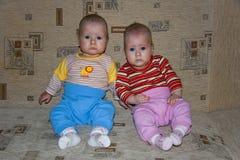 Gemelos jovenes que se sientan en el sofá Foto de archivo