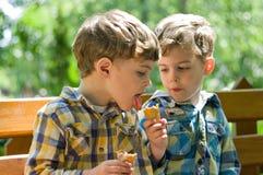 Gemelos que comen el helado Imágenes de archivo libres de regalías