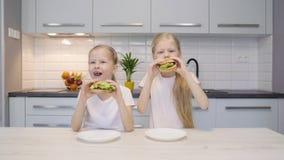 Gemelos que comen las hamburguesas en cocina metrajes