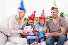 Gemelos que desempaquetan el regalo de cumpleaños con sus padres Imagen de archivo