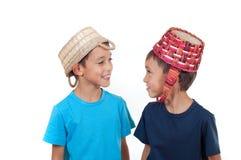 Gemelos que juegan con las cestas de mimbre Fotografía de archivo