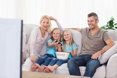 Gemelos y padres que miran la televisión Foto de archivo
