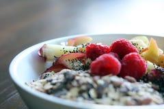Gemengd fruit en graangewas in een witte kom op bruine houten lijst Stock Foto