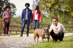 Gemengd rasmeisje die aan huisdier haar hond hurken tijdens een familiegang in het platteland die aan camera, lage hoek kijken royalty-vrije stock fotografie