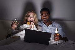 Gemengd raspaar die op enge film in bed op laptop letten royalty-vrije stock afbeeldingen