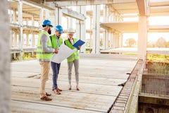 Gemengd team van jonge ingenieurs die vorderingen in het werk betreffende een grote bouwwerf inspecteren royalty-vrije stock afbeeldingen