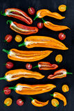 Gemengd van half rode en gele peper met een groene tak dichtbij kersentomaat op zwarte backround Hoogste mening stock fotografie