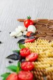 Gemengd van twee gekleurde deegwaren dichtbij tomaten, knoflook en basilicum op grijze houten achtergrond Sluit omhoog ruw Royalty-vrije Stock Afbeelding