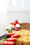 Gemengd van twee gekleurde deegwaren dichtbij tomaten, knoflook en basilicum op grijze houten achtergrond Sluit omhoog ruw De rui Stock Foto