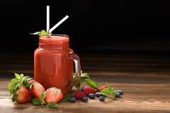 Gemengde bes smoothie in glas met gesneden bessen op hout royalty-vrije stock foto
