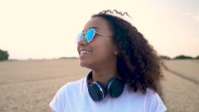 Gemengde de tiener jonge vrouw die van het ras Afrikaanse Amerikaanse meisje haar celtelefoon en draadloze hoofdtelefoons met beh stock videobeelden