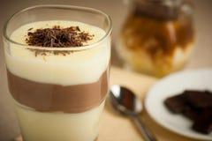 Gemengde die chocolade en vanillepudding in een verfraaid glas wordt gediend stock fotografie