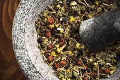 Gemengde droge kruiden in mortier of stamper, gezond aftreksel royalty-vrije stock foto