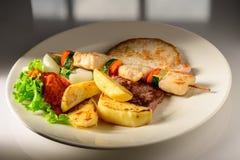 Gemengde Geroosterde die vlees en groenten op een plaat klaar om in restaurant worden gediend wordt verfraaid royalty-vrije stock afbeelding