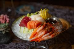 Gemengde gesneden vissensashimi en garnalen op ijs in zwarte kom Sashimi Salmon Tuna Hamachi Prawn en Brandings Kalme reeks, ruwe royalty-vrije stock afbeelding