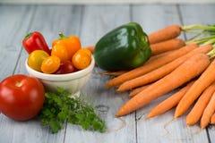 Gemengde groenten Wortelen, paprika, kersentomaten in een kom, een tomaat en kruiden op een keuken houten lijst stock foto's