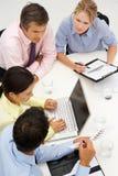 Gemengde groep in commerciële vergadering rond lijst Stock Foto