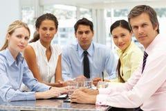Gemengde groep in commerciële vergaderings rondgehangen lijst royalty-vrije stock foto