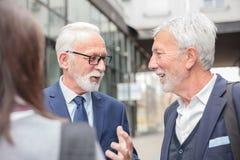 Gemengde groep zakenlui die en voor een bureaugebouw samenkomen bespreken royalty-vrije stock foto