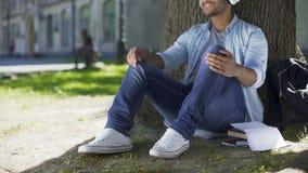 Gemengde jonge mens die aan muziek in hoofdtelefoons onder boom luisteren, het glimlachen, plezier stock footage