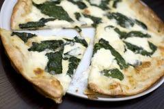 Gemengde kaas en spinaziepizza stock foto's