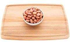 Gemengde noten in een metaal bruine kom op een witte houten scherpe raad royalty-vrije stock foto