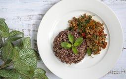 Gemengde ongepelde rijst en gebraden die varkensvlees met basilicumbladeren wordt gehakt op whi royalty-vrije stock afbeelding