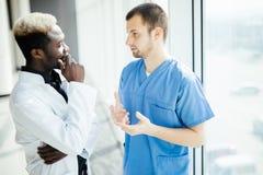 Gemengde race twee Artsen die aangezien zij door het Ziekenhuis lopen spreken stock afbeelding