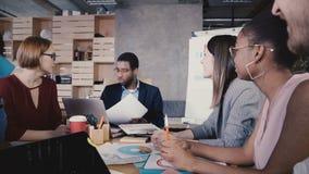 Gemengde ras bedrijfsmensen die in bureau samenkomen De secretaresse geeft documenten aan werkgever, spreidt hij hen onder werkne stock video
