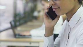 Gemengde ras bedrijfsvrouw die op smartphone in bureau spreken, de routine van de het werkdag stock footage
