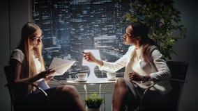 Gemengde ras bedrijfsvrouwen die de tekst van contract in bureau bespreken terwijl het zitten bij de de lijst en het drinken koff stock video