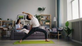 Gemengde ras jonge mens die thuis het doen van yoga uitoefenen wanneer vrouw die op telefoon babbelen stock video