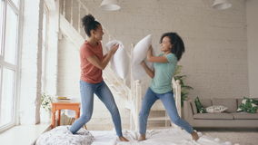 Gemengde ras jonge mooie meisjes die thuis op bed en strijdhoofdkussens springen die pret hebben stock video