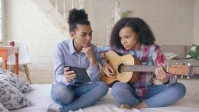 Gemengde ras jonge vrouw die met de zitting van de tabletcomputer op bed haar tienerzuster onderwijzen om akoestische gitaar thui stock videobeelden