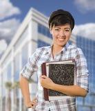 Gemengde Ras Vrouwelijke Student Holding Books voor de Bouw Stock Foto's