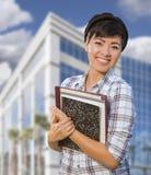 Gemengde Ras Vrouwelijke Student Holding Books voor de Bouw Stock Fotografie