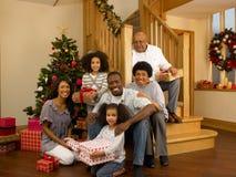 Gemengde rasfamilie met Kerstboom en giften Stock Afbeelding