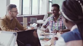 Gemengde rasgroep architecten op commerciële vergadering in modern bureau Mannelijke Afrikaanse teamleider die ideeën bespreken