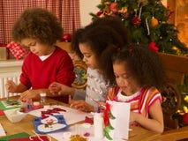 Gemengde raskinderen die Kerstkaarten maken Stock Fotografie