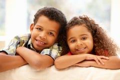 Gemengde rasmeisje en jongen thuis stock foto's